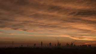 Timelapse shot of clouds sailing and sun rising over Frankfurt, Germany. Distant buildings silhouettes and sky in warm lights