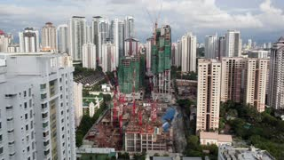Timelapse shot of construction works in residential area of Kuala Lumpur with high-rise apartment blocks. Clouds sailing over the city and night coming