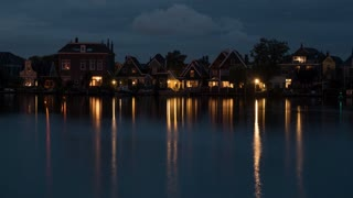 Timelapse shot of evening changing night in Dutch village. Electric lights in house windows reflecting in water in the darkness