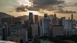 Timelapse shot of Hong Kong at sunset and in the evening. Cityscape with high-rise buildings and water transport traffic in the harbour