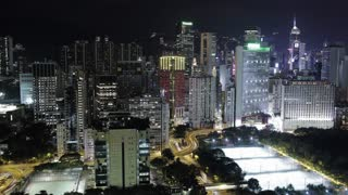 Timelapse shot of illuminated Hong Kong. Night city view with concrete jungle, road interchange and football fields