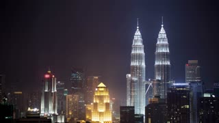 Timelapse shot of illuminated skyscrapers and Petronas Twin Towers in night Kuala Lumpur, Malaysia