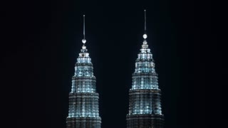 Timelapse shot of illuminated tops of Petronas Twin Towers with light going down. The world highest twin towers. Kuala Lumpur, Malaysia