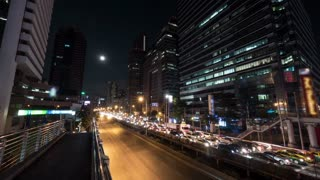 Timelapse shot of night Bangkok street. Intense transport traffic on the road with highrise buildings alongside. The moon and sailing clouds in dark sky