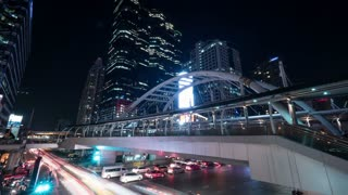 Timelapse shot of night transport traffic on the road with pedestrian bridge and illuminated highrise buildings in Bangkok, Thailand