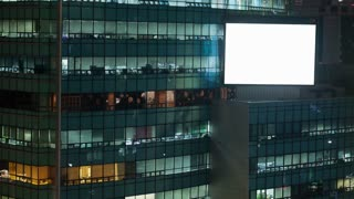 Timelapse shot of people working in business centre and big blank advertising screen on the building at night. Seoul, South Korea