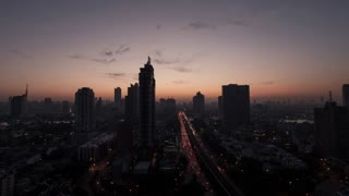 Timelapse shot of sun rising over Bangkok, Thailand. Dawn in the capital city with intense traffic and high-rise architecture