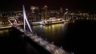 Timelapse shot of transport traffic in Erasmus Bridge and ship sailing along the river on background of illuminated buildings of Rotterdam at night