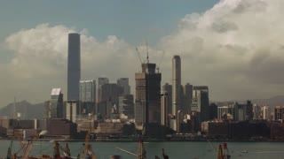 Timelapse shot of waterside Hong Kong in day time and at night. Clouds sailing over the city during the day and illumination of buildings at night