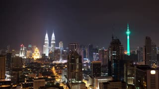 Timelapse shot with zooming in of Kuala Lumpur at night. Capital of Malaysia with illuminated skyscrapers, Petronas Twin Towers and Menara KL Tower
