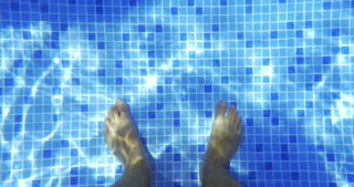 Top view of mans feet standing on the bottom of blue tiled swimming pool. Sunlight refracting through the clear water