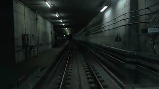 Train starts moving in dark underground tunnel, cabin view to rail tracks
