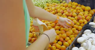 Unseen woman is picking apricots from the big pack and putting them into paper bag