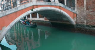 VENICE, ITALY - FEBRUARY 16, 2015: Traditional Venetian gondola boat is sailing under the bridge over the water canal. Some tourists in carnival masks are on board.