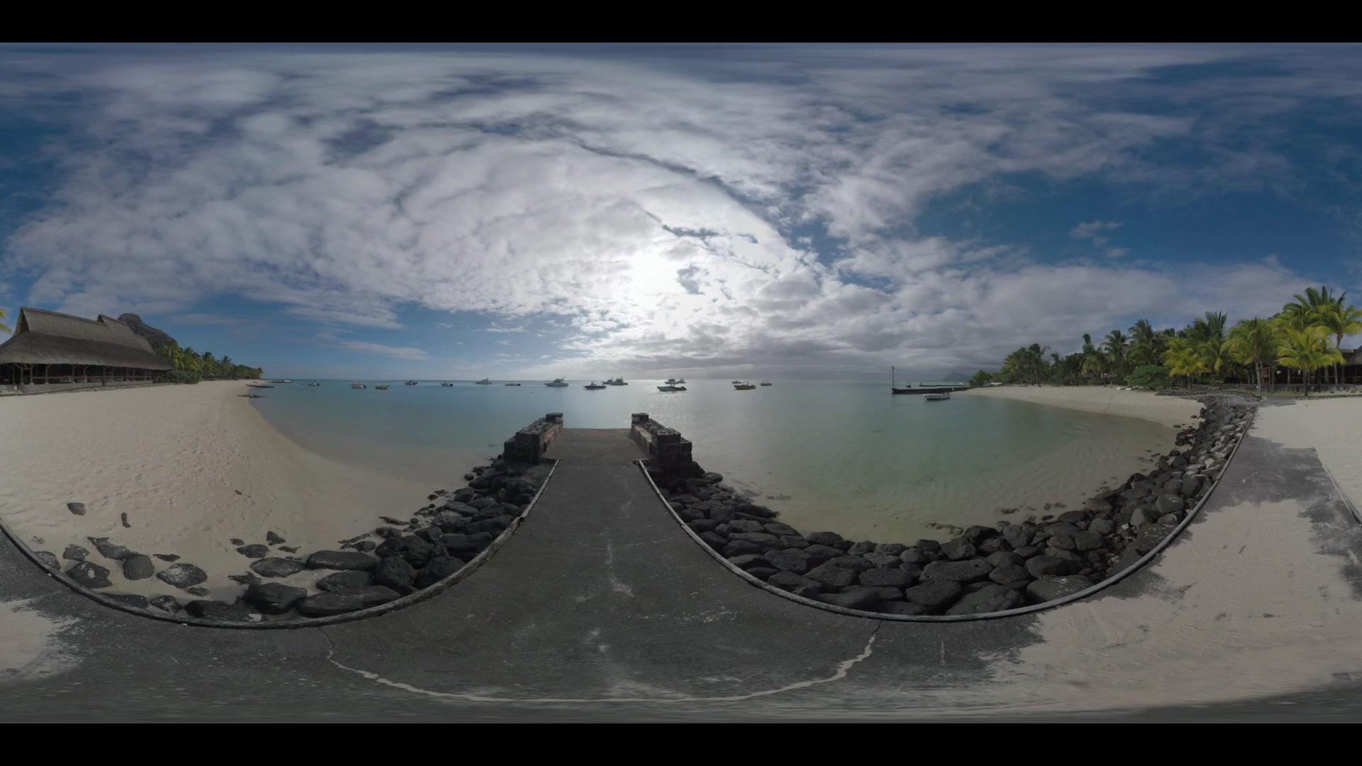 360 VR video. Beach with palms and pier leading into the shallow ocean water with many yachts and motor boats. Mauritius scene