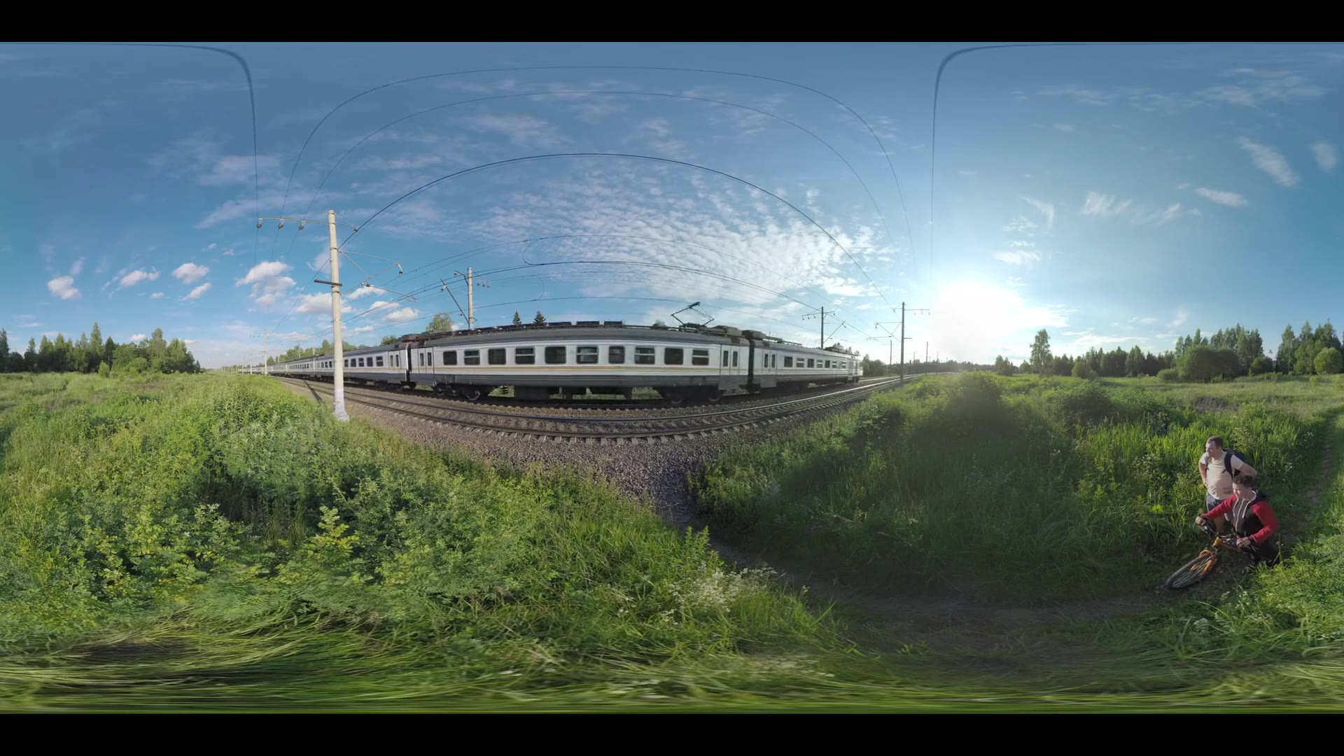 360 VR video. Countryside in bright sunlight. Father and son with bike waiting for the suburban train to pass and crossing the rails. Ruza in Moscow region, Russia