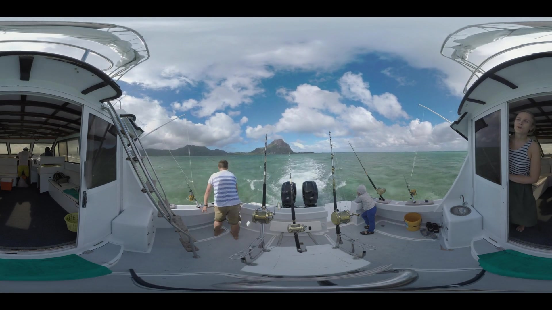 360 VR video. Dad and son standing on the back of the yacht with fishing-rods fixed near the motors. They looking at ocean and distant Mauritius Island, mother enjoying the view from the cabin. Family water travel