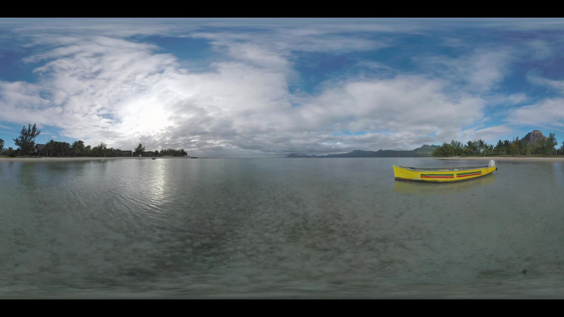 360 VR video. Landscape of Mauritius on cloudy day. View to the boat in shallow ocean water, coast with palms and mountains with Le Morne Brabant