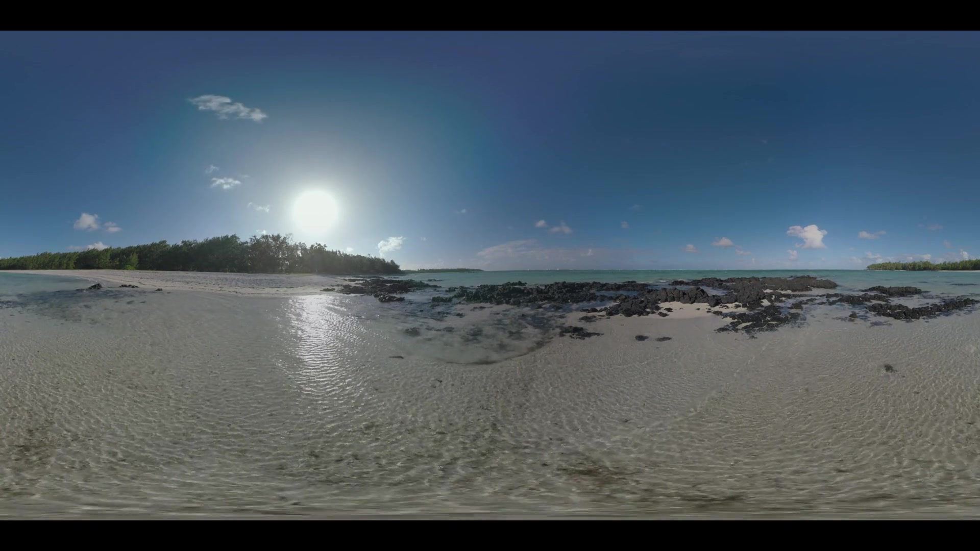 360 VR video. Mauritius waterscape. Shallow waters of the ocean and black volcanic rocks on the coast with green trees alongside