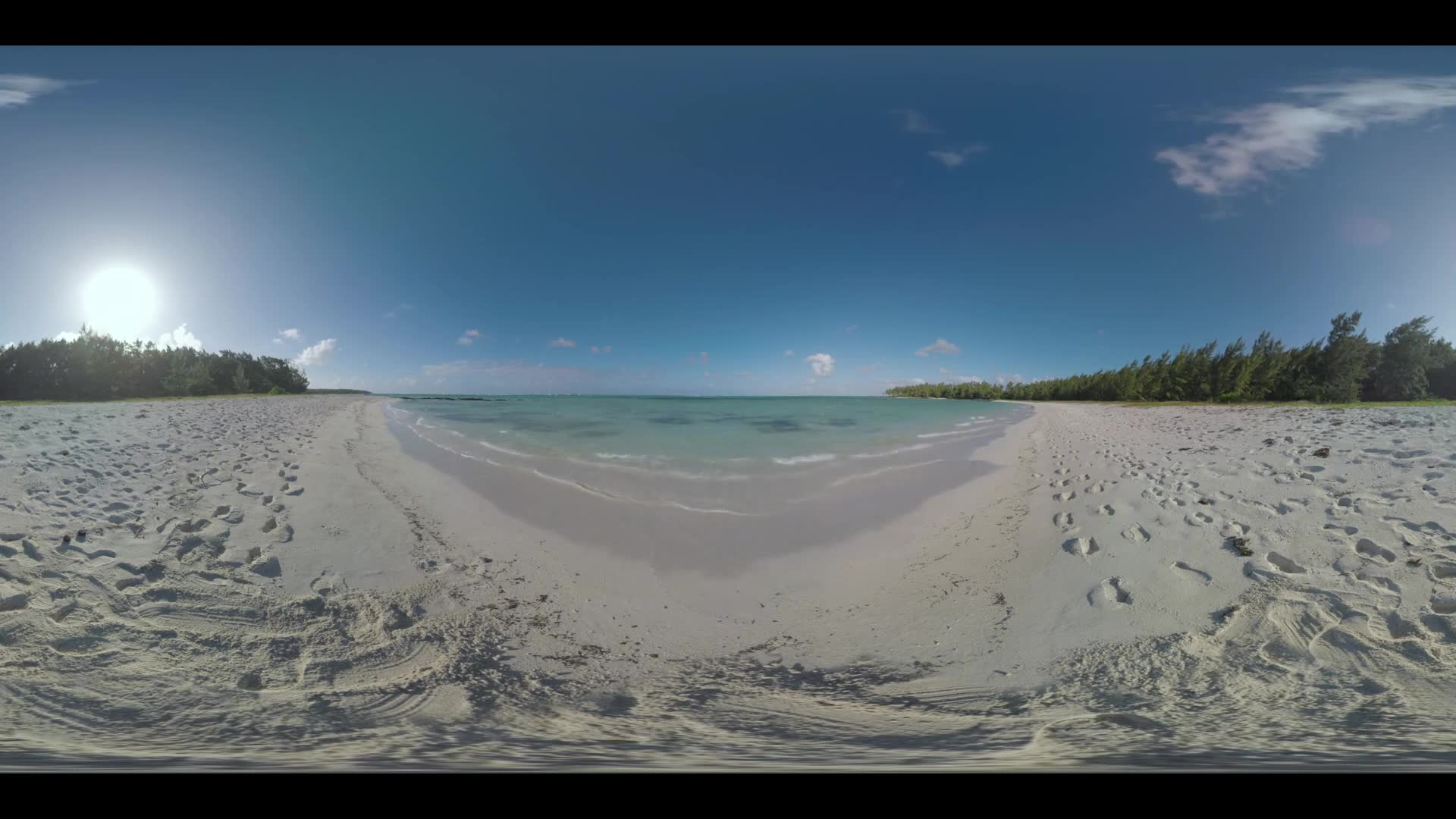 360 VR video. Nature scene of Mauritius Island. View to the clear blue ocean, beach with footprints and green trees along the coast. Bright sun shining in the sky
