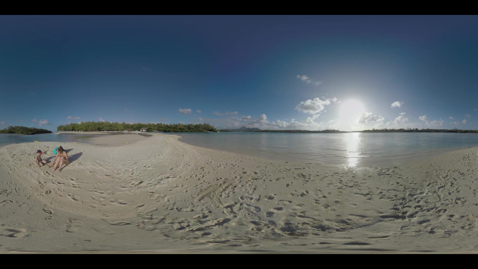 360 VR video. Parents and son having a nice day on the beach. Mom and child relaxing on the shore while dad swimming. Water shining in bright sunlight. Vacation on resorts of Mauritius