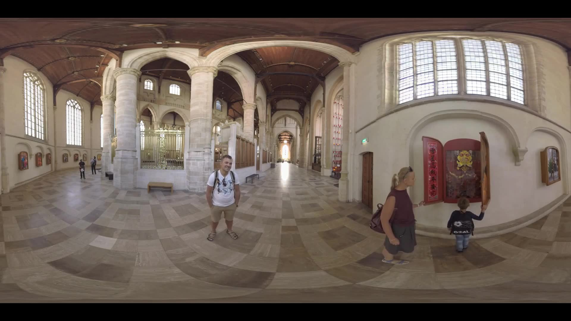 360 VR video. Parents with child (with model release) and other visitors opening shutters and looking at installations of different cultures and holidays inside St. Lawrence Church