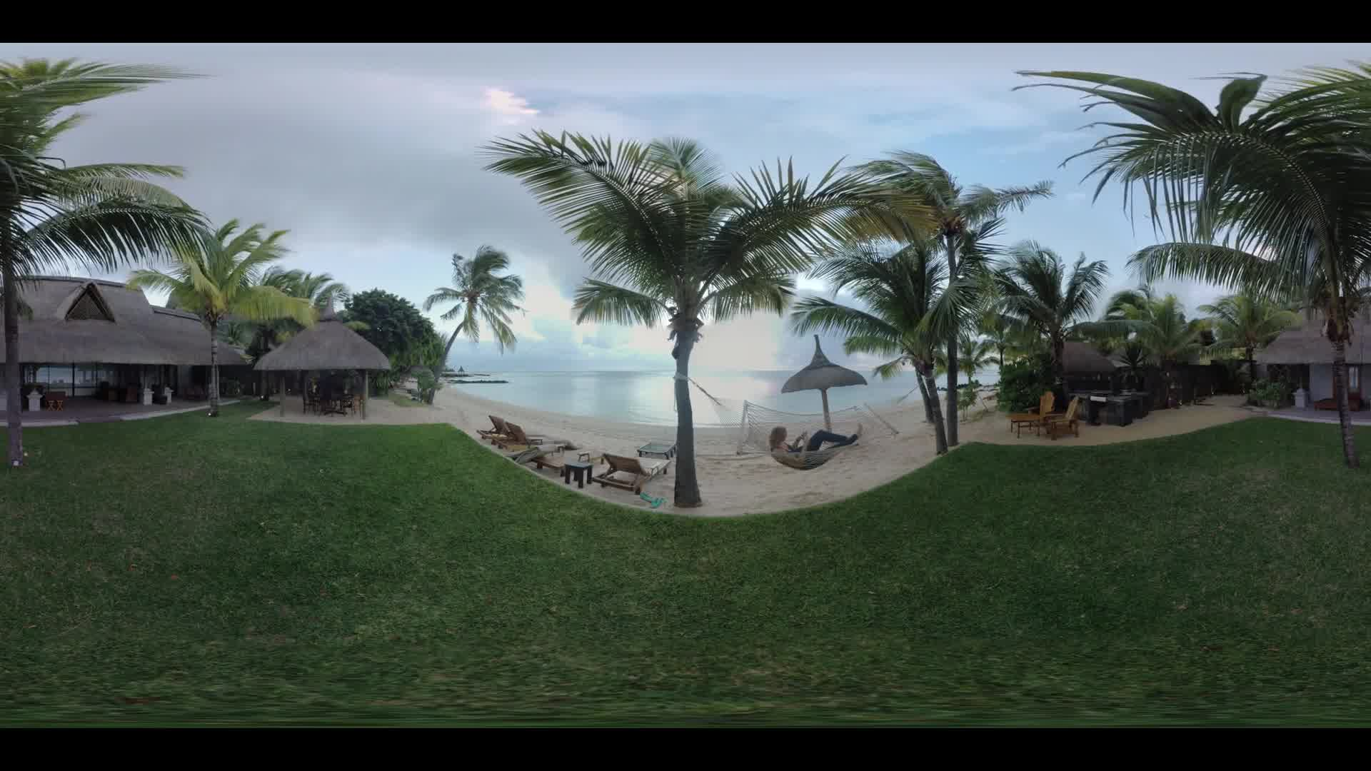 360 VR video. Scene with guest house on the ocean coast in tropics and woman relaxing in hammock with cellphone, Mauritius. Vacation at the seaside