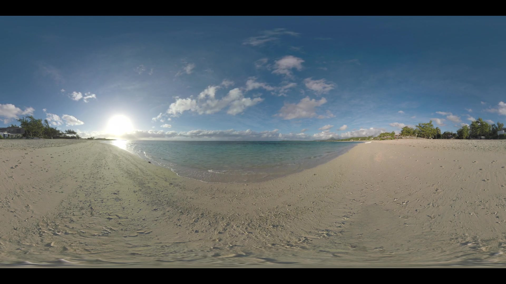 360 VR video. Summer vacation scene with clear blue ocean, beach and bright sunshine. Mauritius coast view with trees and houses alongside
