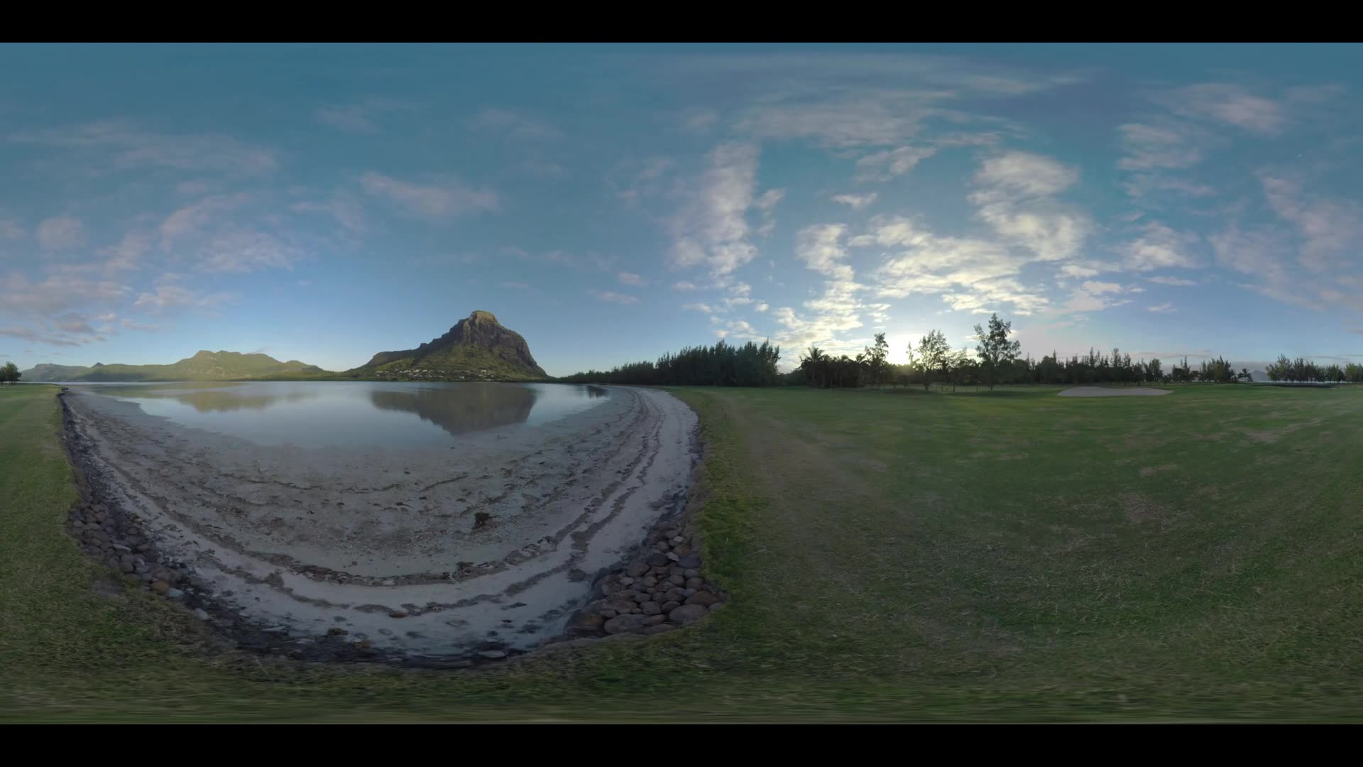 360 VR video. Timelapse shot of clouds sailing over Le Morne Brabant peninsula with waterside view to the mountains and golf course with driving cart. Sunset time, Mauritius