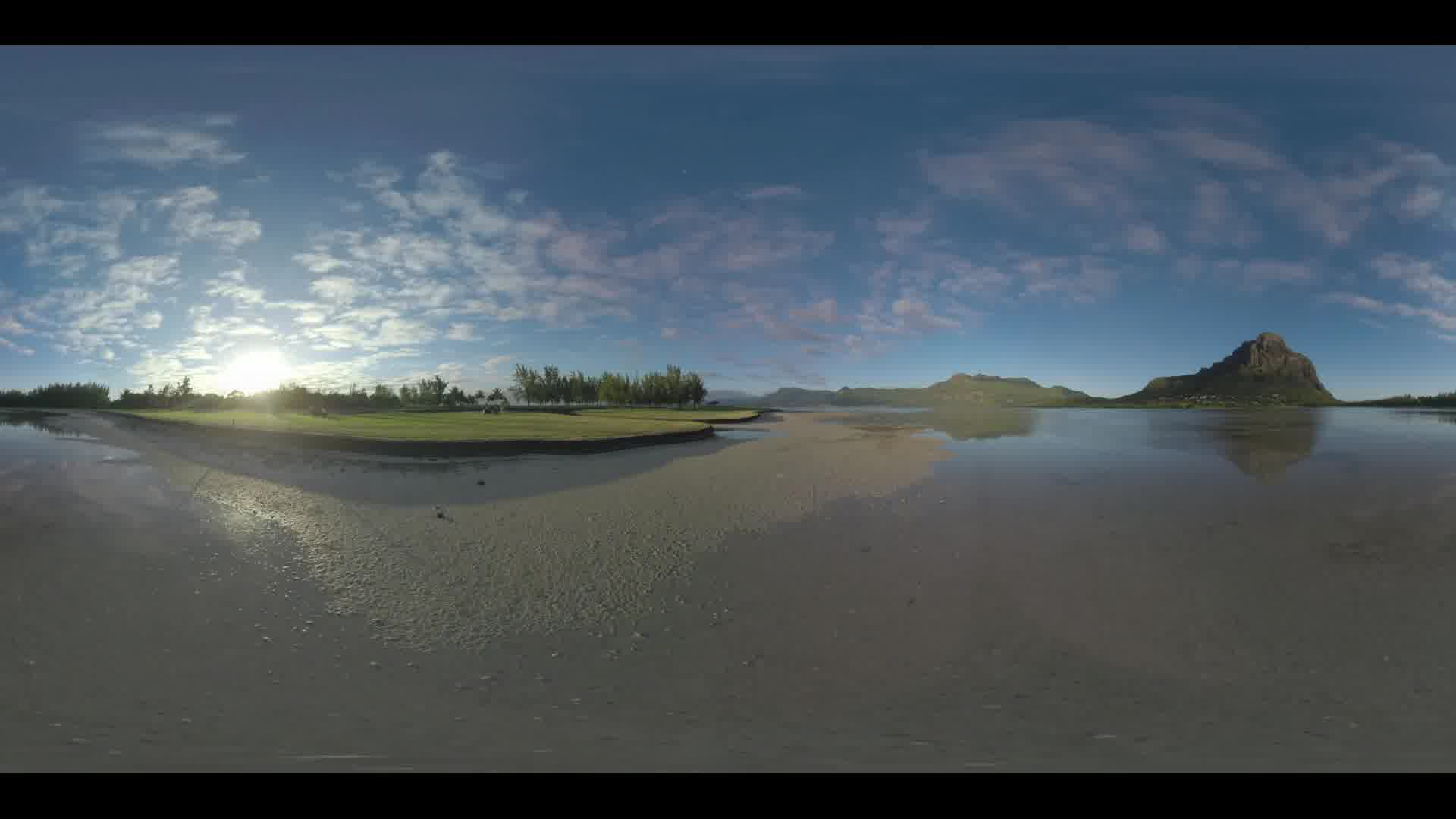 360 VR video. Timelapse shot of clouds sailing over mountains and Le Morne Brabant. Carts driving on waterside golf course, bright evening sun shining. Mauritius landscape