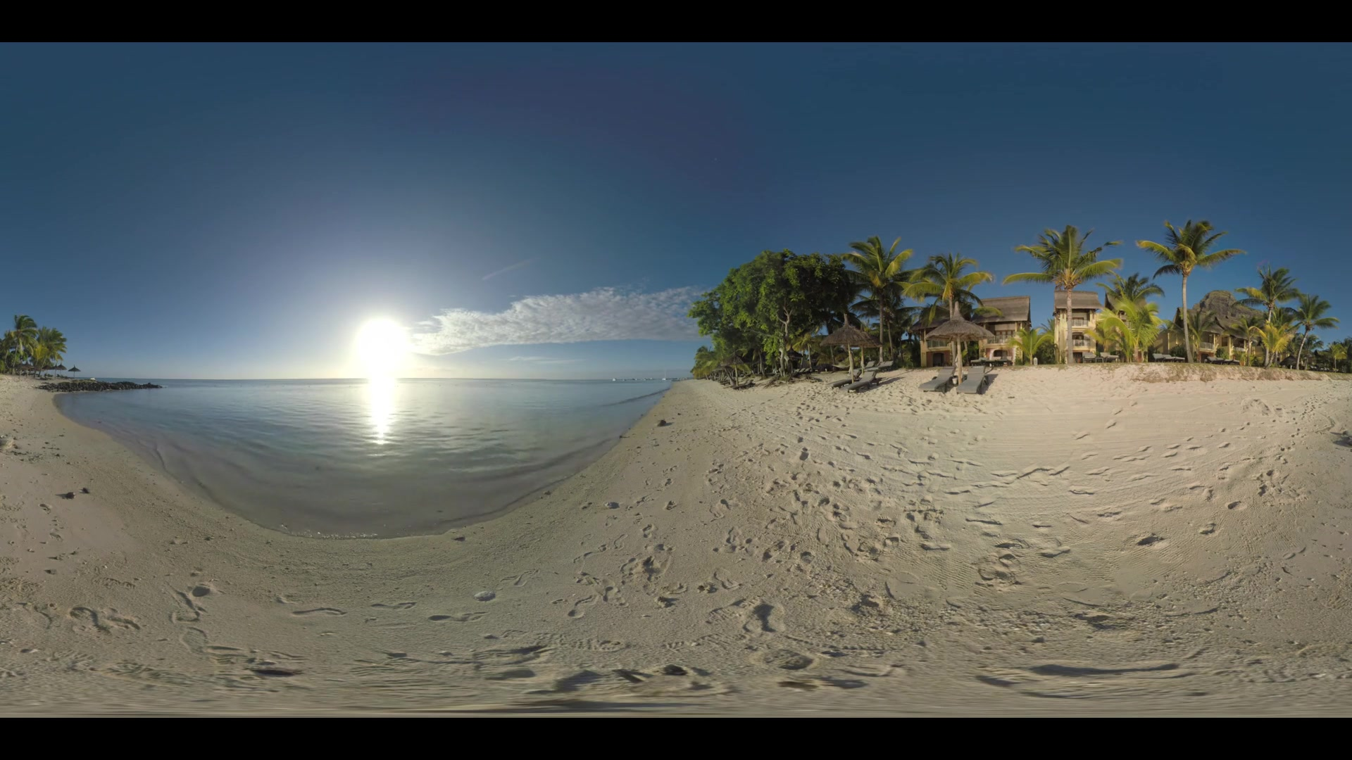360 VR video. Vacation scene of tropical resort with hotels, chaise-longues and straw umbrellas on the ocean coast. Bright sun shining over the water and reflecting there, Mauritius