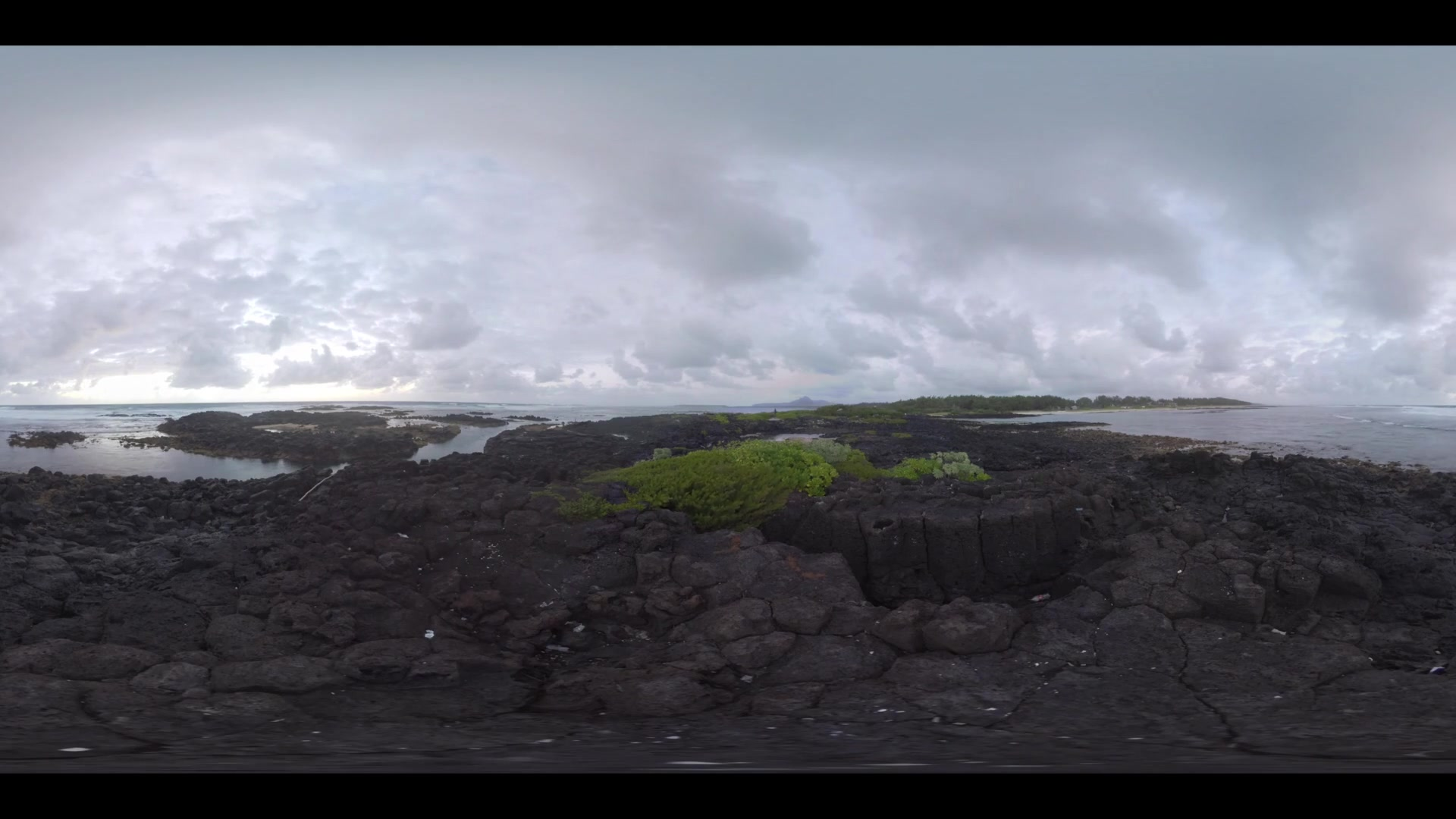 360 VR video. View from the black volcanic rocks to the ocean and distant coast with green trees. Cloudy sky over Mauritius island