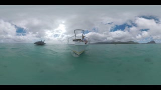 360 VR video. View to the sailing yacht with man on front deck sailing around famous stone islet not far from Mauritius Island. Landscape of Mauritius mountains with Le Morne Brabant
