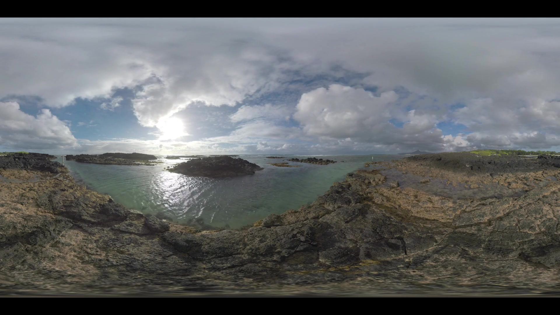 360 VR video. Waterscape and landscape of Mauritius. Ocean shallow water and black rocks on the coast, clouds sailing over the island