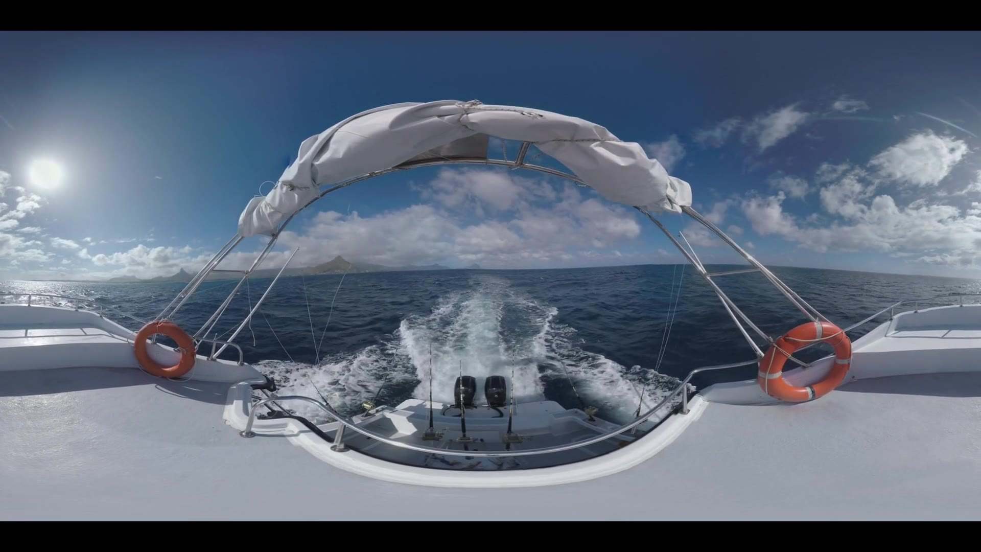 360 VR video. White yacht sailing in the ocean, view to the distant mountains on of Mauritius Island and vast ocean from the upper deck. Fishing-rods fixed at the back of the motor boat