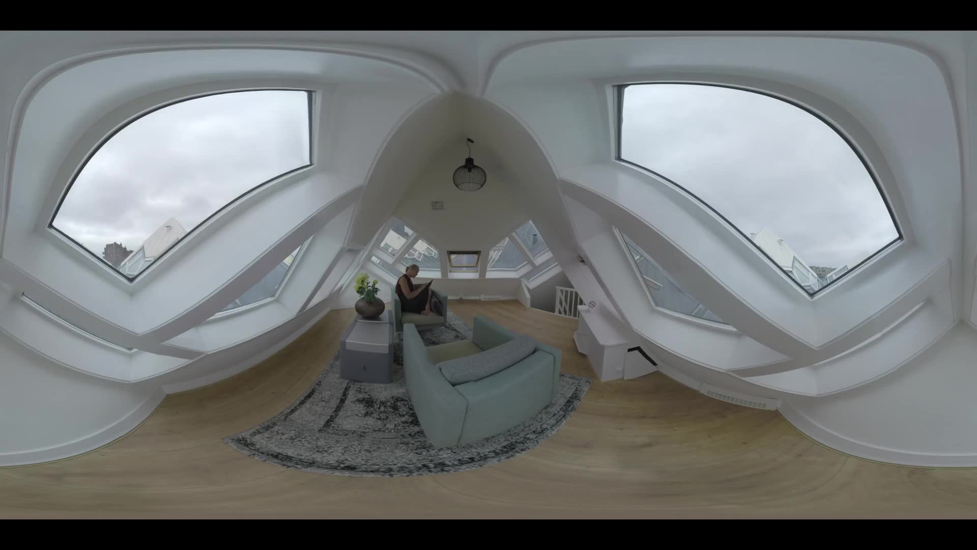 360 VR video Woman using tablet computer in Cube House. She sitting in the armchair, then walking around and looking out of window. View to the room interior upstairs. Rotterdam, Netherlands