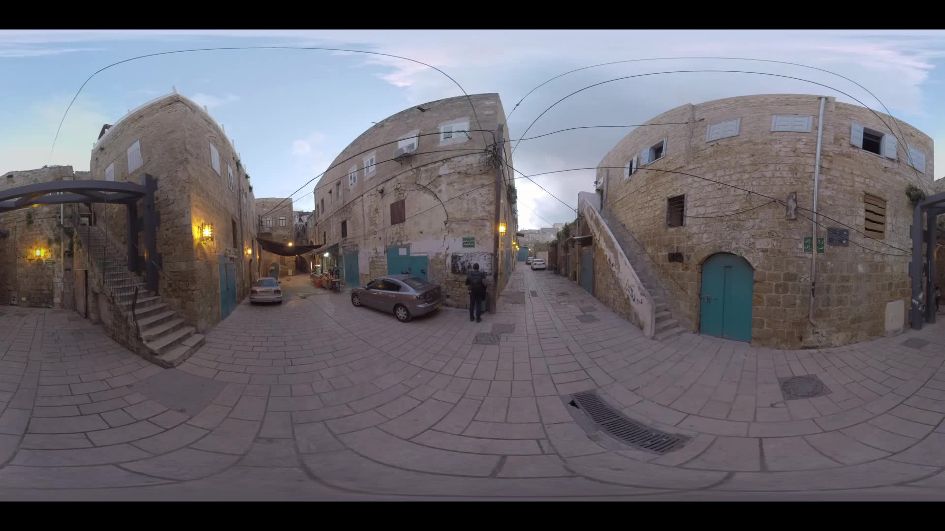 ACRE, ISRAEL - MARCH 13, 2017: 360 VR video. Evening view of narrow street with old stone houses, several cars and vendor. One of the world oldest cities, continuously inhabited since the Middle Bronze Age some 4000 years ago