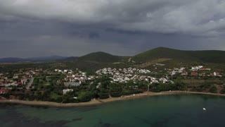 Aerial view of coastal town Trikorfo Beach in Greece on overcast day. Flying over the sea, beach and cottages. Scene with green hills and dark heavy clouds