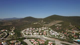 Aerial view of town with cottages among green hills, transport traffic on the road. Scene of Trikorfo Beach, Greece