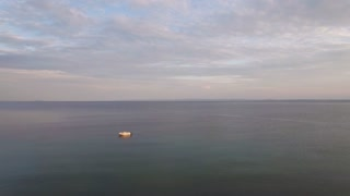 Aerial view of vast quiet sea with a single empty boat. Waterscape and cloudy sky