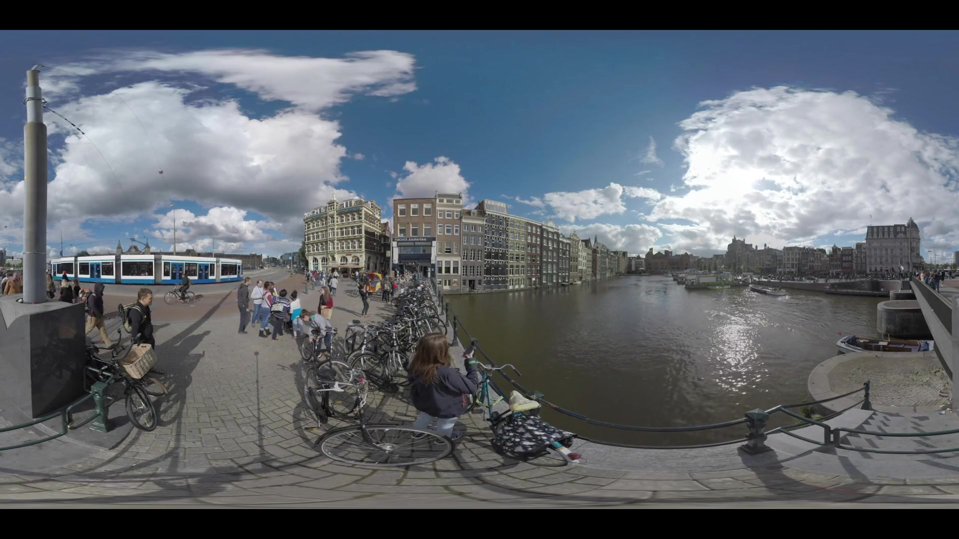 AMSTERDAM, NETHERLANDS - AUGUST 09, 2016: 360 VR video. City scene with Dutch houses, canal with boats starting their tour and Rijksmuseum. People walking on sidewalks, traffic on the motorway