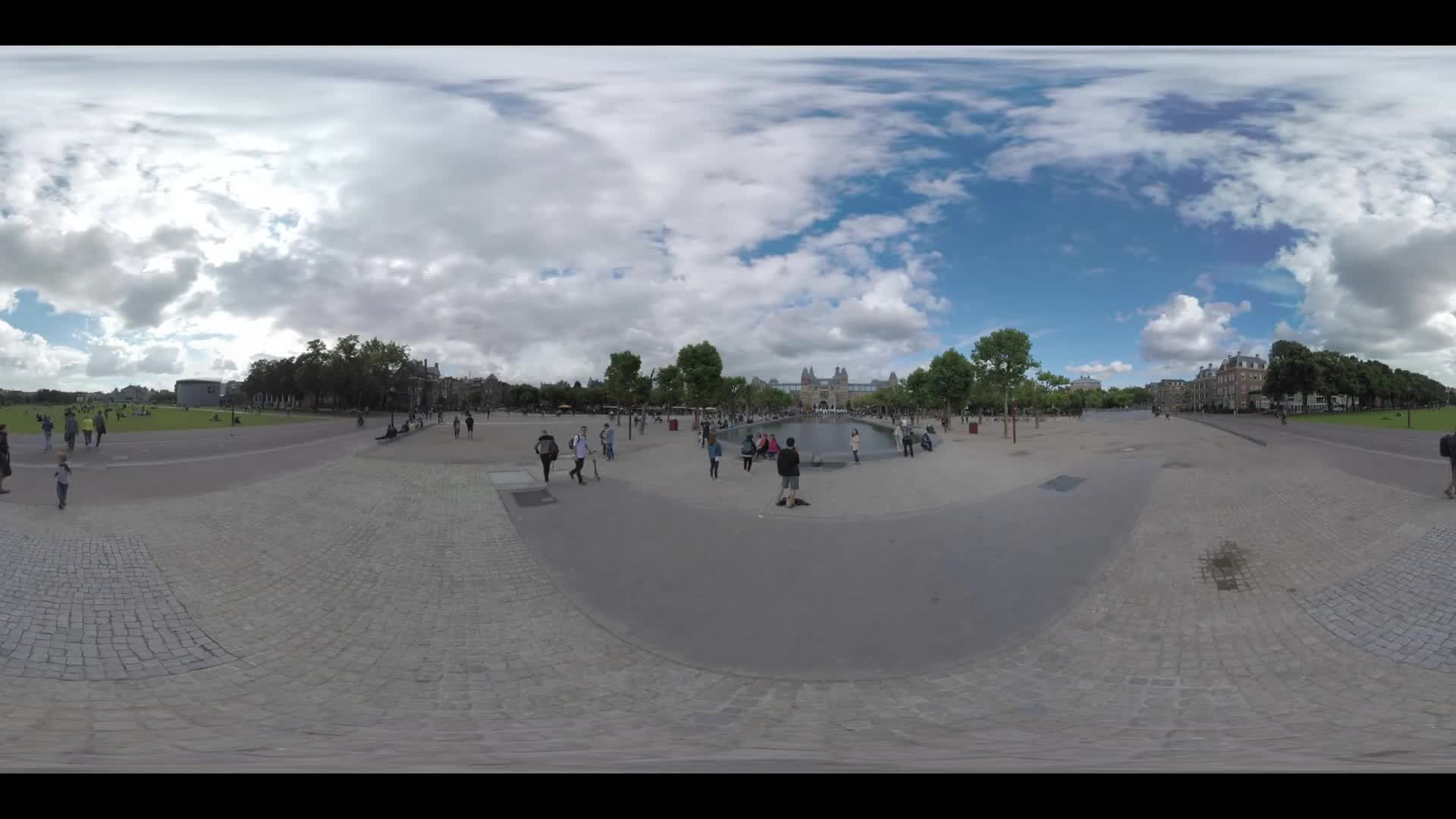 AMSTERDAM, NETHERLANDS - AUGUST 09, 2016: 360 VR video. City view with Rijksmuseum and people walking at Art Square and green Museumplein