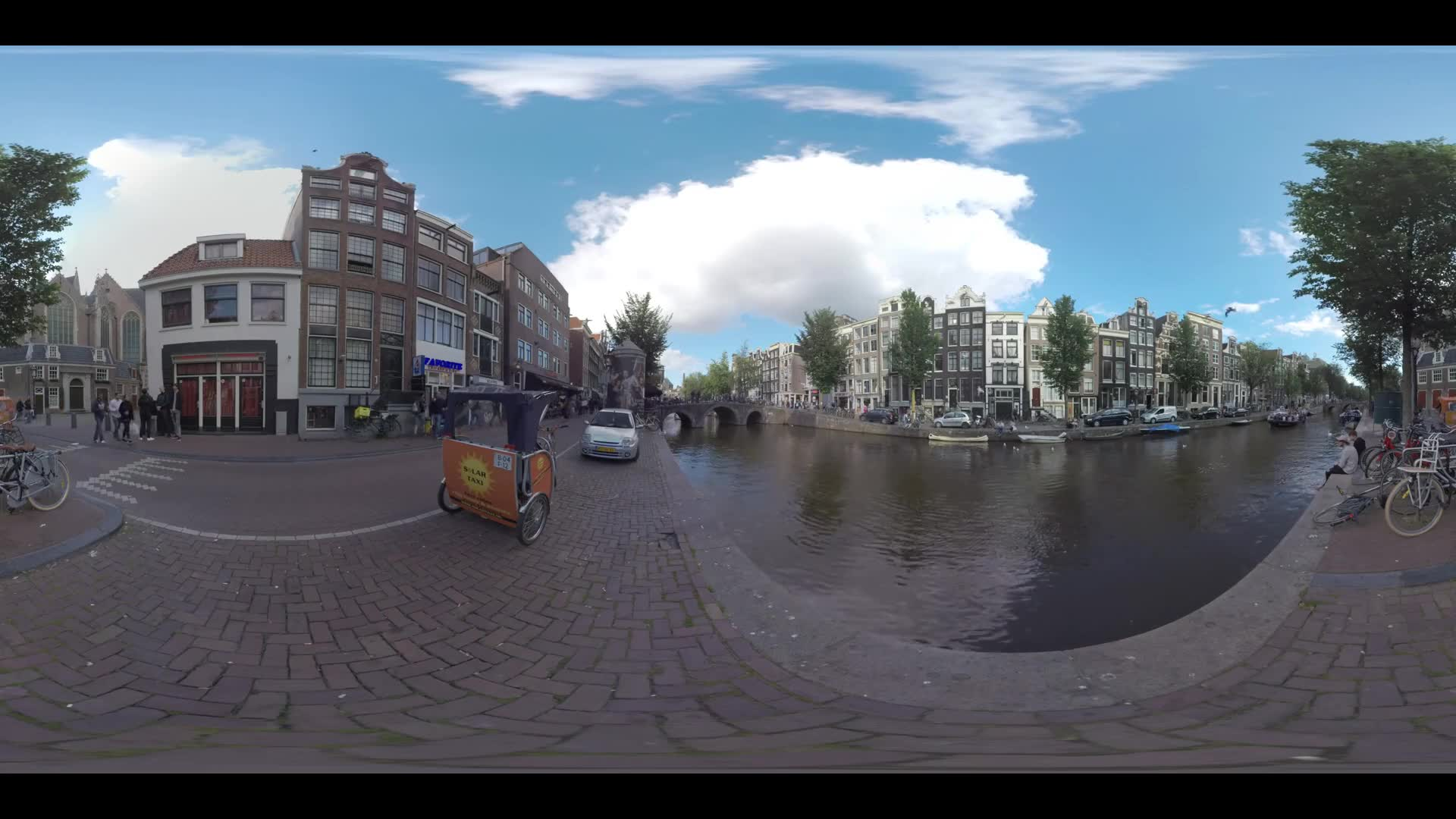 AMSTERDAM, NETHERLANDS - AUGUST 09, 2016: 360 VR Video. Dutch capital cityscape with canal, waterside houses and view to 800-year-old Oude Kerk