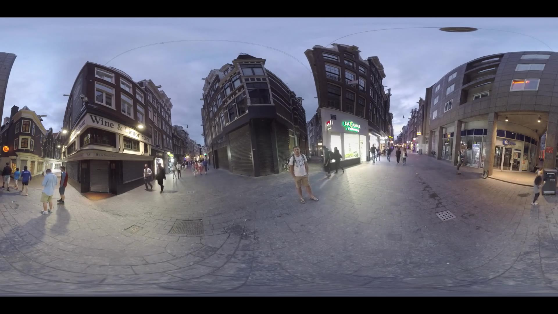 AMSTERDAM, NETHERLANDS - AUGUST 09, 2016: 360 VR video. Evening view to the alleys between houses and people walking among illuminated stores and banners