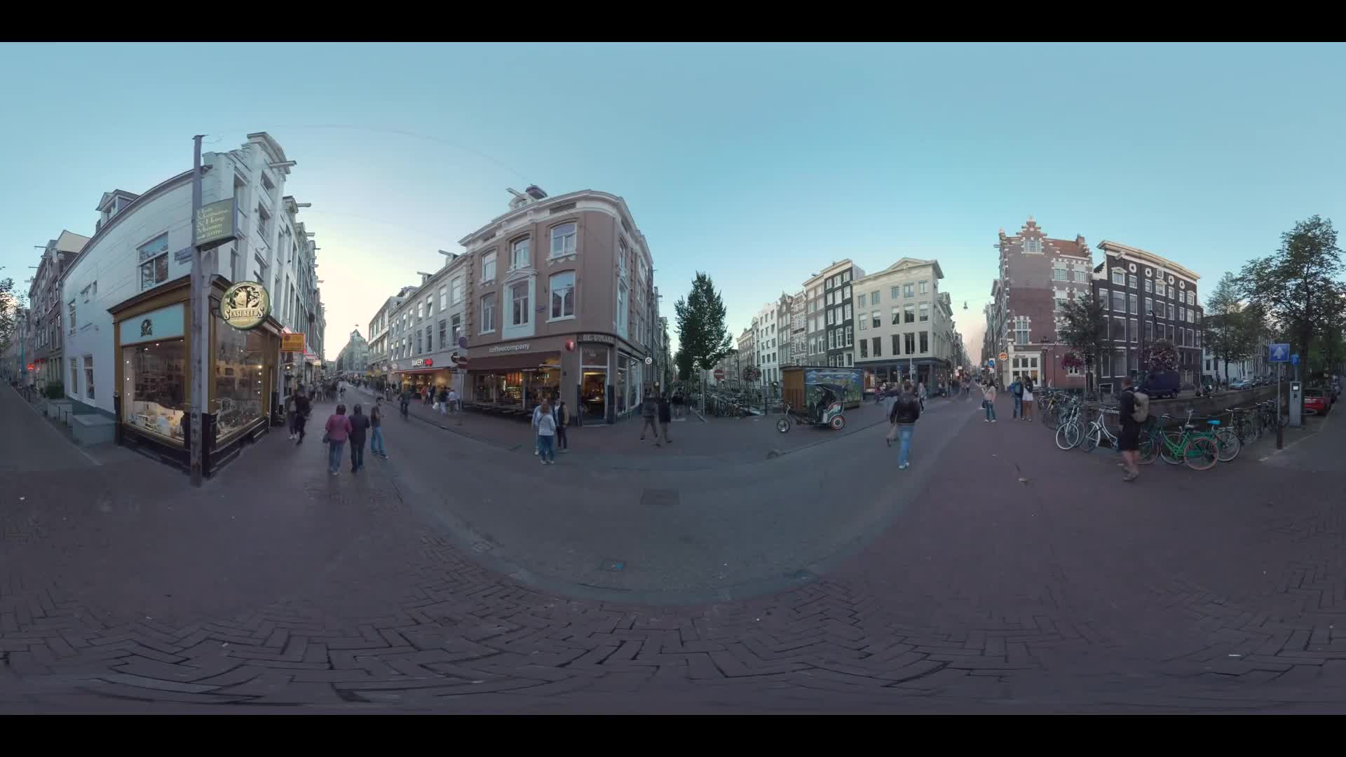 AMSTERDAM, NETHERLANDS - AUGUST 09, 2016: 360 VR video. Oude Doelenstraat with stores and cafes and people walking there. View with houses, canal and parked bikes