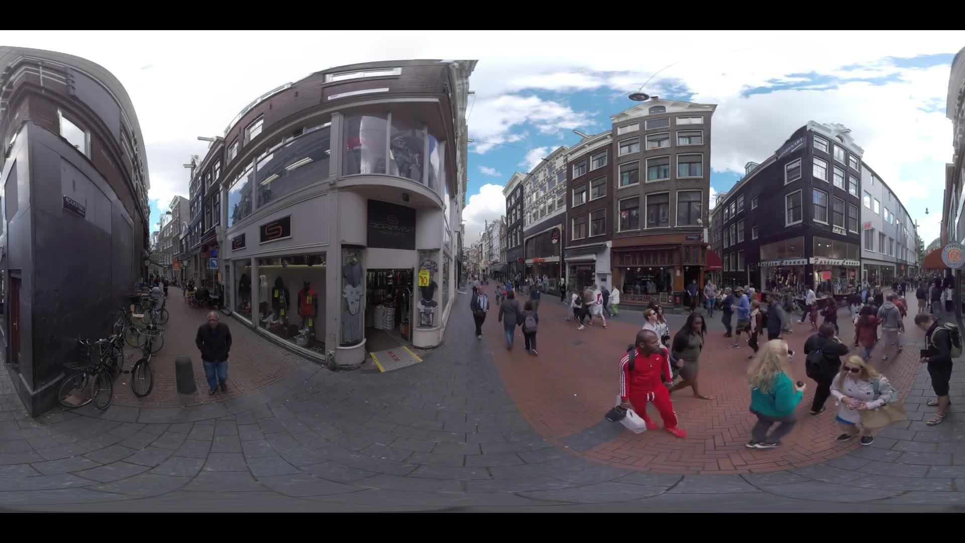 AMSTERDAM, NETHERLANDS - AUGUST 09, 2016: 360 VR Video. People traffic in the paved alleways with stores and cafes located on ground floors of the houses
