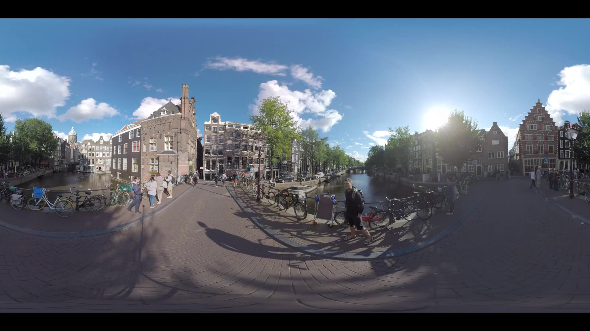AMSTERDAM, NETHERLANDS - AUGUST 09, 2016: 360 VR Video. People walking across Armbrug leading over the canal. Cityscape with waterside street and Dutch houses