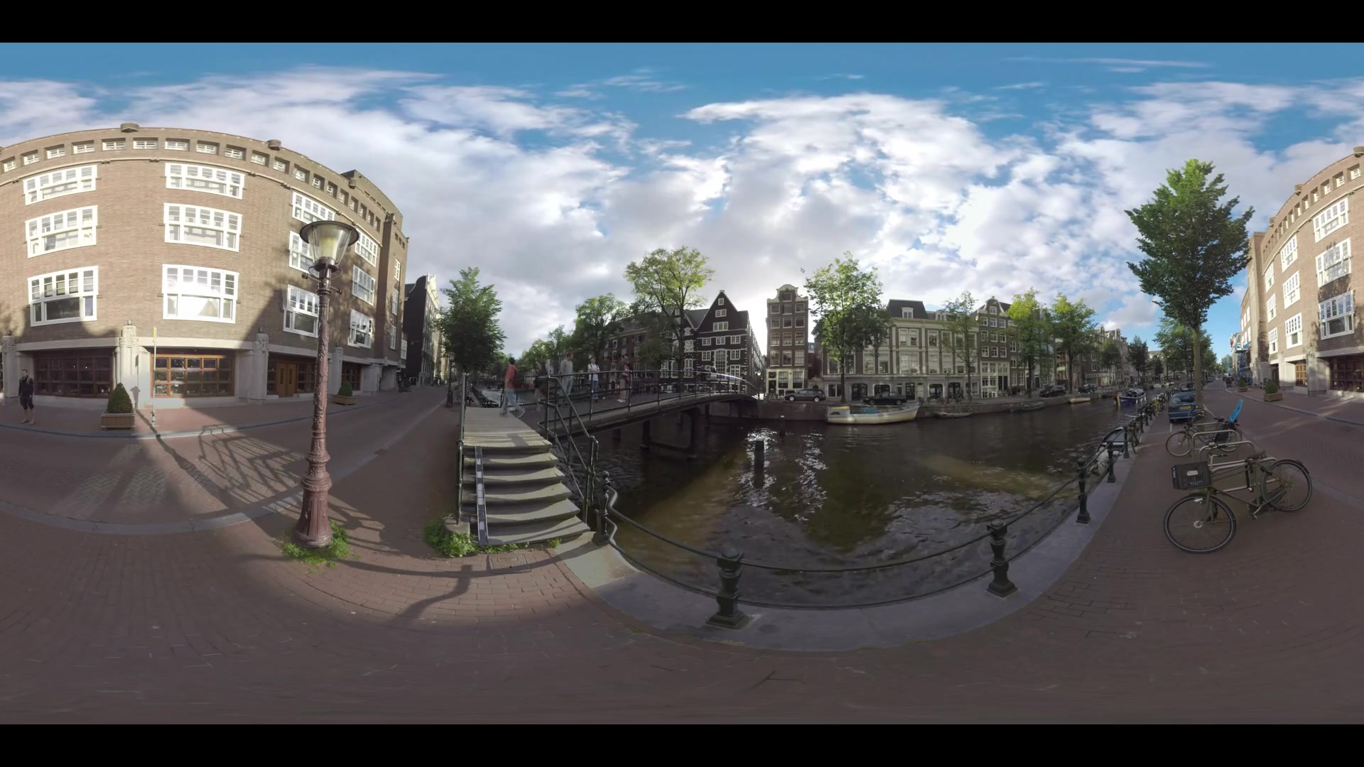 AMSTERDAM, NETHERLANDS - AUGUST 09, 2016: 360 VR video. Quiet city street with traditional Dutch houses and people walking across the footbridge over the canal where touristic boat sailing