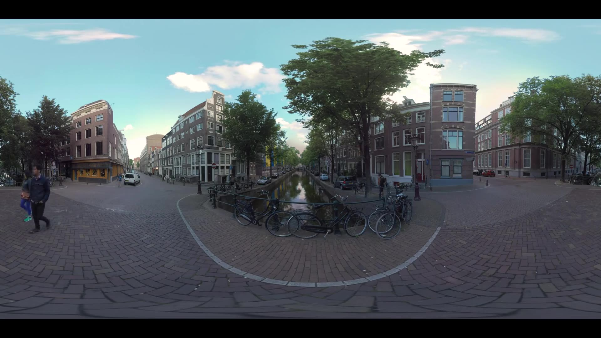 AMSTERDAM, NETHERLANDS - AUGUST 09, 2016: 360 VR video. Quiet city streets with houses alongside. View to the canal, parked bikes and people walking across the bridge