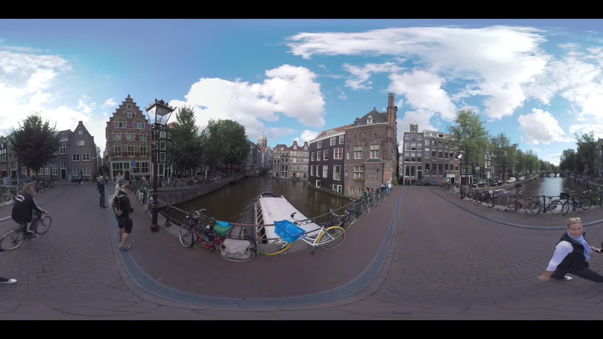 AMSTERDAM, NETHERLANDS - AUGUST 09, 2016: 360 VR Video. View from Armbrug to the canal, streets and Dutch houses. People walking on footbridge and touristic water bus sailing under it